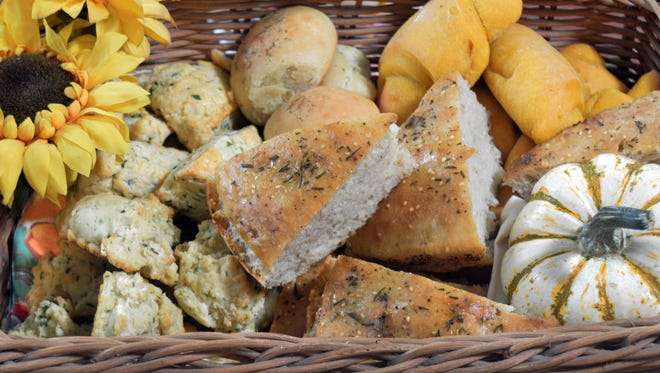 Assorted breads like biscuits,scones, pan rolls, focaccia and crescents mingle in a Thanksgiving bread basket.