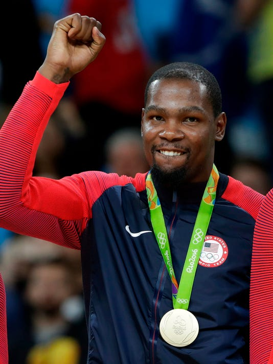 FILE - In this Aug. 21, 2016, file photo, Kevin Durant poses with his gold medal for men's basketball during the medals ceremony at the 2016 Summer Olympics in Rio de Janeiro, Brazil. LeBron James is putting himself in position to play in a fourth Olympics, and Kevin Durant and Chris Paul a third. The NBA stars were among the headline names on the list of 35 players chosen Friday, April 6, 2018, for USA Basketball's national team pool of players for 2018-20. (AP Photo/Eric Gay, File)