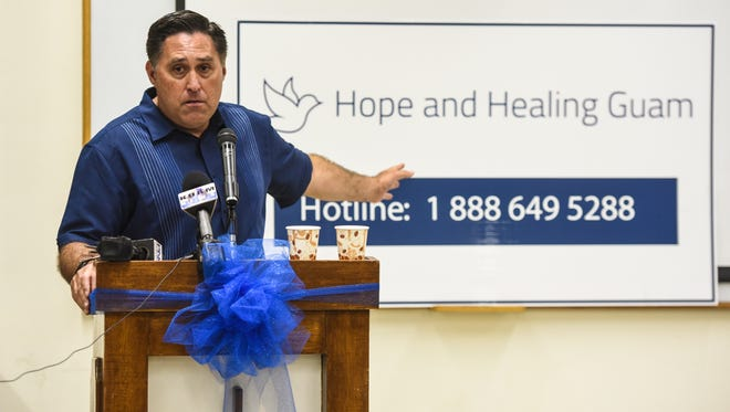 In this April 11 file photo, Michael Caspino motions toward a hotline number during a press conference at the Archdiocese of Agana. Caspino is the executive director of Hope and Healing Guam.