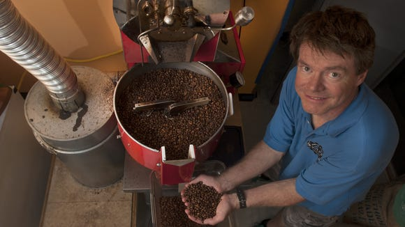 Co-owner Steve McFadden shows some fresh coffee beans from his roasting machine at the Revolution Coffee Roaster in Collingswood.