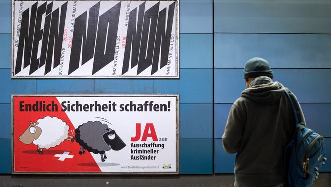 """This Feb. 9, 2016, photo shows posters campaigning for and against the """"Enforcement Initiative"""" in Zurich, Switzerland."""