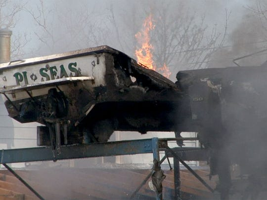 Firefighters battle a fire in a rack of boats at the
