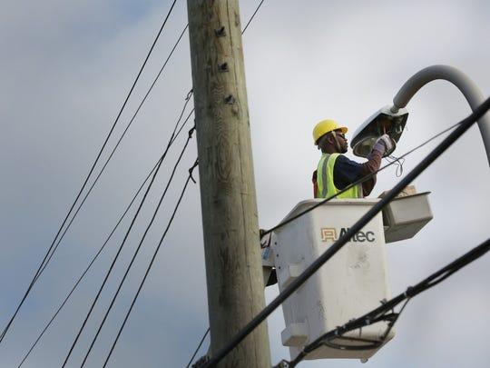 A Detroit Public Lighting Department crew maintains street lights on Warren Avenue in 2013.