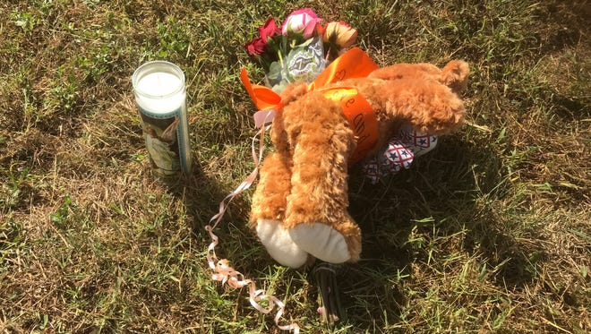 """A candle, 12 roses and a teddy bear with an orange ribbon bearing the words """"love and support"""" sit just beyond the First Baptist Church of Sutherland Springs, Texas, on Nov. 6, 2017."""