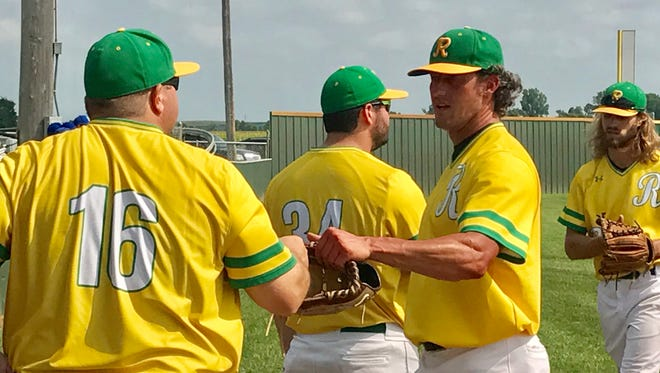 Renner Monarchs manager Kevin Knetsch (16) congratulates pitcher Kris Regas after the left-hander threw 8 shutout innings in Saturday's amateur baseball state tournament.