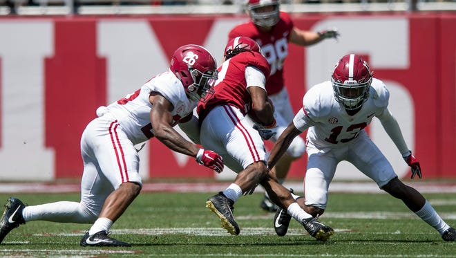 Alabama defensive back Kyriq McDonald (26) and defensive back Nigel Knott (13) stop wide receiver Xavian Marks (19) during the A-Day Game at Bryant-Denny Stadium on the University of Alabama campus in Tuscaloosa, Ala. on Saturday April 21, 2018.