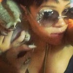 Rihanna snuggles with a loris in Thailand.