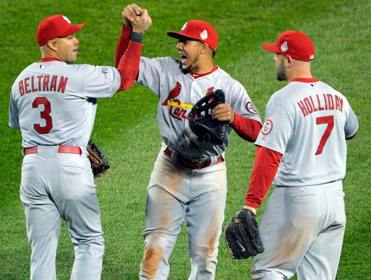 Cardinals outfielders Carlos Beltran, Jon Jay and Matt Holliday celebrate beating the Red Sox at Fenway Park.