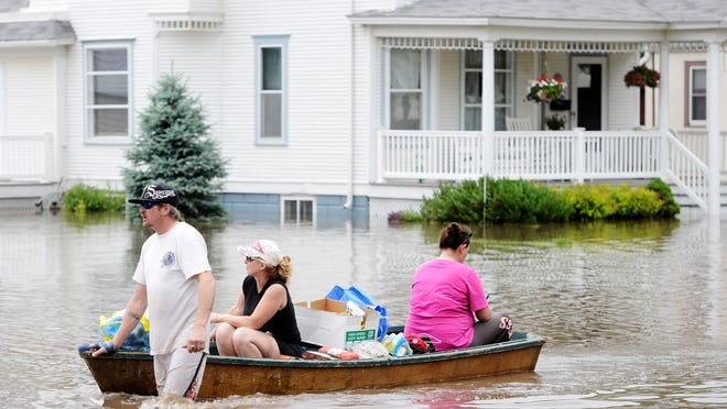 David Dixon pulls Heather Dixon and Dawn Suhr in a boat down Main Street in Rock Valley on Monday afternoon after retrieving some valuables out of their flooded houses.
