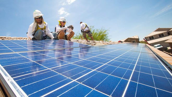 Workers install solar panels on a Cave Creek home as Arizona's rooftop-solar industry continues growing. SolarCity's Tinh Nguyen (from left), Dylan Robins and Michael Armin install solar panels on a Cave Creek home. APS seeks to trim customers' solar credits.