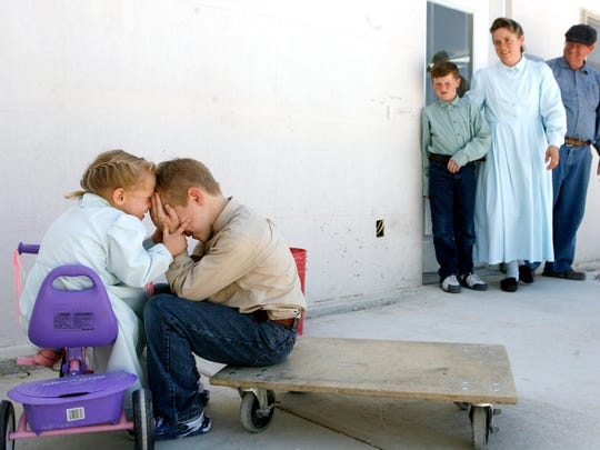 Anne, 3, and Ephraim, 7, play around as brother Zachery, 9, mother, Zavenda Young and father Edson Jessop watch the two outside the wood shop at the Yearning for Zion Ranch near Eldorado on June 4, 2008.
