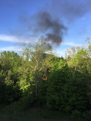 Smoke rose above the treeline from the abandoned, Burlington, Kentucky property starting at about 7 p.m. The property is situated in a wooded area behind condos on Paraon Mill Drive, and contained old cars and farm equipment.