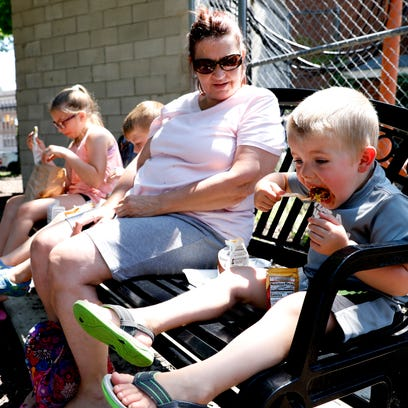 Miles Carroll, 3, takes a bite of a walking taco as