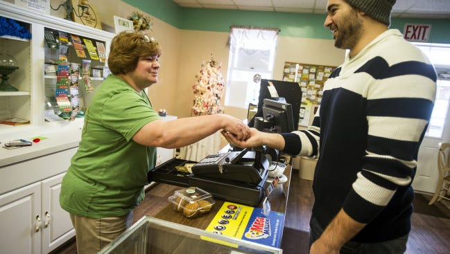 Matt Gracey, of Hanover, purchases pumpkin cream cookies from Karen Rider, owner of Sweet Treats Bakery of Hanover, on Baltimore Street in Penn Township. Rider has owned the business since July 1 but opened the bakery in September.