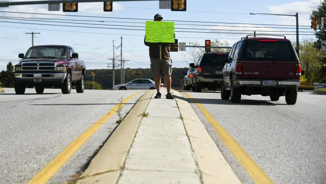 With his sign, Jason Mangus, of West Manheim Township, asks passersby to not to give to panhandlers at Baltimore Pike and Brunswick Drive in West Manheim Township. Mangus is opposed to panhandlers asking drivers for money at the median and that they are sending a wrong message to children.