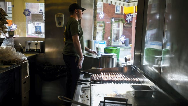 Famous Hot Weiner employee Bill Sweeney works in downtown Hanover on Dec. 10. Peter Alexopoulos, known by locals as 'Uncle Pete,' died Dec. 7 at 91 years old. Alexopoulos worked for many years at Famous Hot Weiner, running the grill, and cooking hotdogs and burgers for customers.