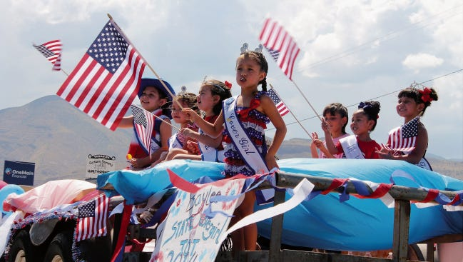 In this file photo, children wave American flags during the annual Fourth of July parade in 2014.