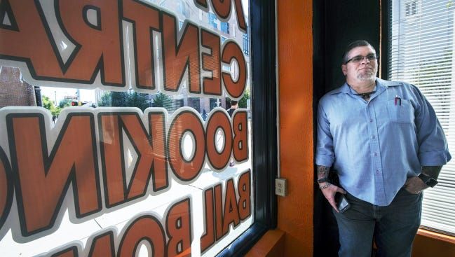 Michael Hansen Sr. stands in his business, Central Booking Bail Bonds. He had been charged in January burglary, theft by extortion and related offenses.He now faces additional theft charges in an unrelated case.