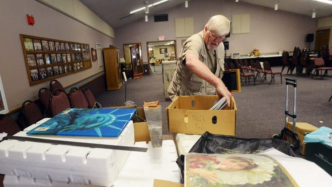 Bob Kolbe sorts through a box of photographs and magazines Friday afternoon while preparing for an auction of historical memorabilia at Sunnycrest United Methodist Church.