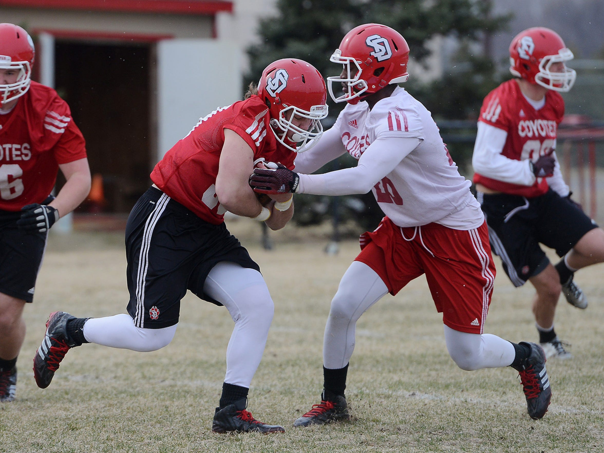 Shay Bratland tries to carry the ball past Chris Tyler