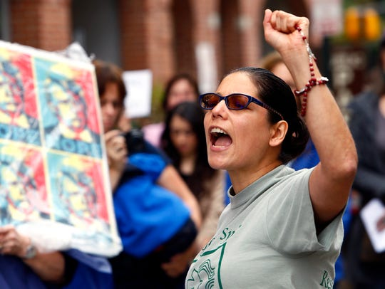 Karol Ruiz of Wind of the Spirit leads a chant as Immigrant