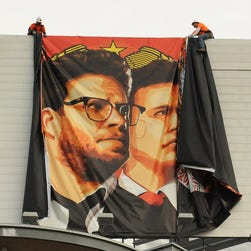 "Workers remove a poster-banner for ""The Interview"" from a billboard in Hollywood, California, on Thursday."