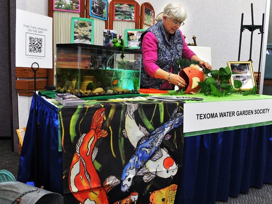 In this file photo, Mary Rhoads sets up the organization's booth at the annual Arts Alive! Home & Garden Festival. The event returns to MPEC's Ray Clymer Exhibit Hall Feb. 23 and 24.