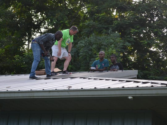 Mike Clohessy and Haitian helpers install the roof-mounted,