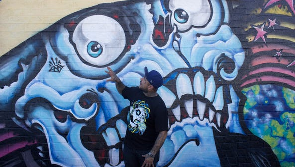 Phoenix muralist Angel Diaz stand in front of a skull