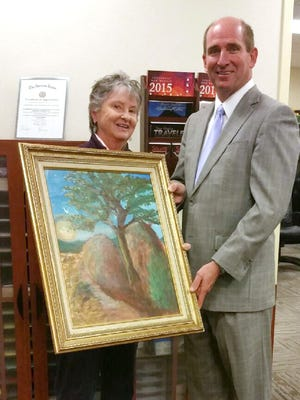 """Local artist Barbara Smith presented a painting of the """"Tree Rock"""" landmark to Western New Mexico University President Joseph Shepard on Tuesday. Smith painted the artwork in December in honor of the November donation of the property by the Robinson family to the university."""