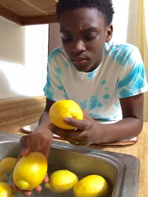 Nasai Oliver, 13, prepares lemonade he will be selling Friday at Frawley Stadium. He's expected to sell his homemade drink several nights this season.