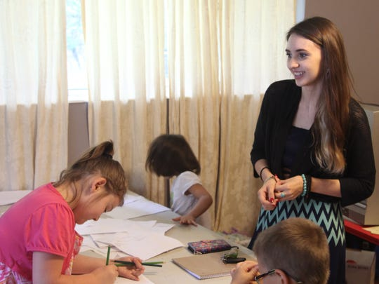 Casi Norris, 24, talks with her adoptive brothers and sisters while they doodle on scrap paper.