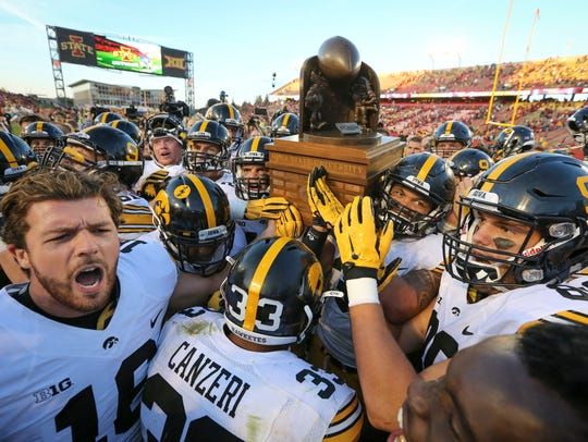 Iowa celebrates with the Cy-Hawk Trophy Saturday, Sept.