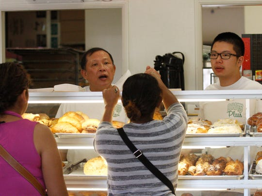 Heng Chauv, the owner of Donuts Plus, and his son James Chauv help customers with their orders Friday at Donuts Plus in Simi Valley.