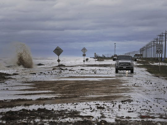 Vehicles navigate past waves and debris washing over