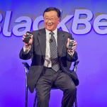 BlackBerry CEO John Chen reveals phones during the news conference for the company's new BlackBerry Classic phone, Wednesday, Dec. 17, 2014, in New York.