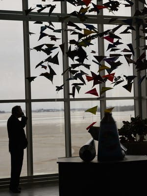 """The fifth annual Art Meets Heart Community Art Project is now on display in the grand lobby of the Austin Straubel International Airport in Ashwaubenon. A traveler waiting for a flight talks on the phone next to this year's community art project called """"Creativity Soars."""""""