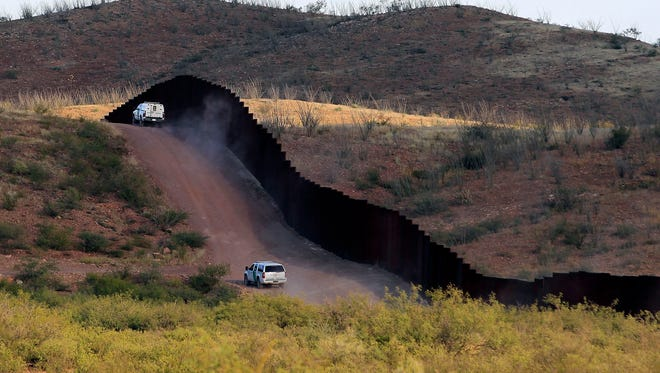 In this Tuesday, Oct. 2, 2012 file photo, U.S. Border Patrol agents patrol the border fence, in Naco, Ariz.