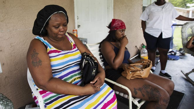 Sherri Flemming, the mother of Michael Kelly is surrounded by family members including, Quanti Johnson, right, at her east Fort Myers home on Wedensday. She confirmed that Kelly was a victim in Lehigh Acres homicide.