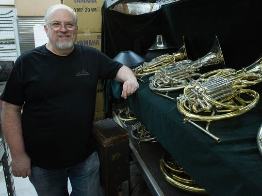 Jim Patterson, owner of Patterson Hornworks, stands next to custom made French horns in his shop, Thursday, June 29, 2017.