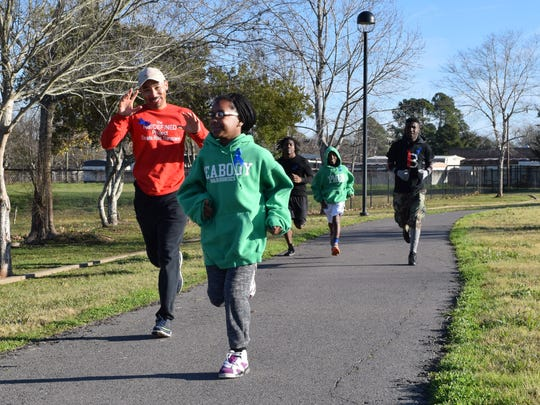 Curtis Lewis (left), organizer of the Redefine Project, and A'Rianna Allen run a couple of laps around the track at Compton Park Saturday. The Redefine Project is a community service organization.