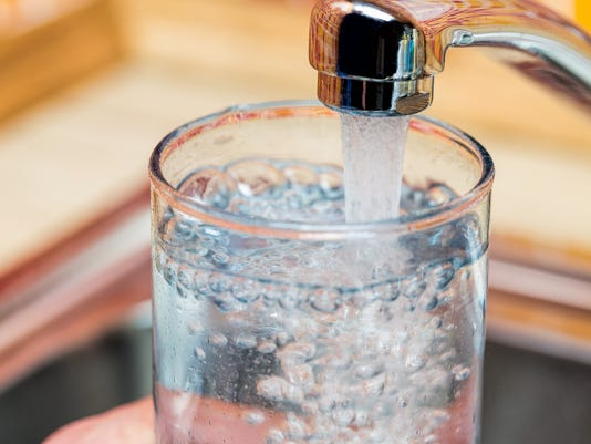 Filling up a glass with drinking water from kitchen tap