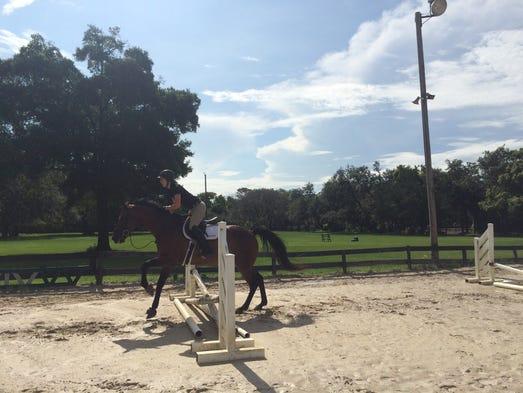 Julie Felsted, a junior management major, jumps a fence
