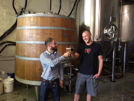 Hi-Wire Brewing's co-owner and head brewer toast to