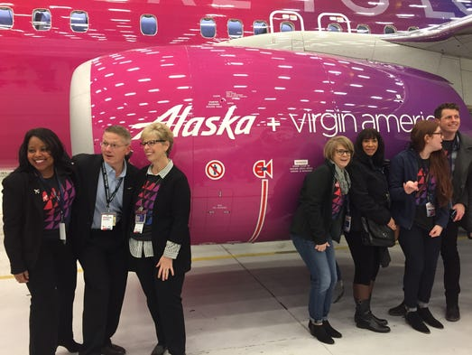 Employees pose near a special-livery 737 that Alaska