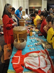 Around 400 students visited the Paragon Casino Resort in Marksville on Friday for a sample of the annual Tunica-Biloxi Pow Wow. Terri Richard (left) talks to students about her collection of Native American objects during the field trip opportunity offered by the Pow Wow committee.
