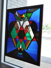 A stained glass painting from the Louisiana State Art Collection hangs in a window at the Alexandria Museum of Art.