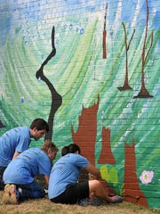 Volunteers from the Mechanics Bank group help paint a mural at Harmony House in August as part of the United Way Day of Caring.