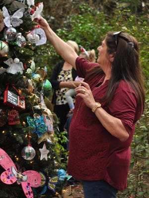 Toni Genova hangs an ornament on the butterfly tree in the Alexandria Zoo on Sunday for Dustin Bordelon.