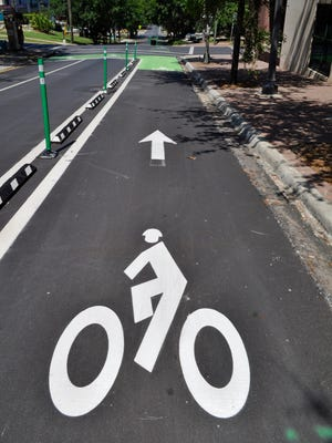 The new bike network, marked off with buffers and bright green paint, aims to keep cyclists safe on city roads.